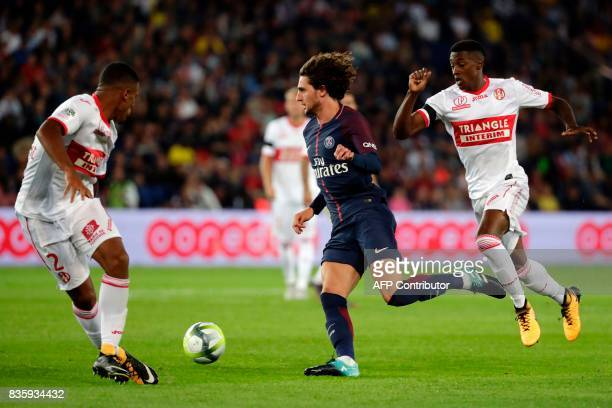 Paris SaintGermain's French midfielder Adrien Rabiot drives the ball next to Toulouse's French defender Kelvin Amian during the French L1 football...