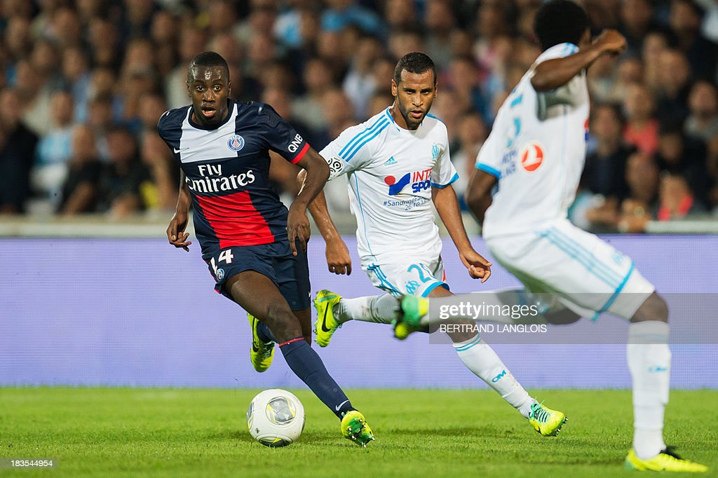 Paris Saint-Germain's French midfielder Blaise Matuidi (L) vies with Marseille's Togolese midfielder Jacques-Alaixys Romao (C) during the French L1 football match Olympique de Marseille vs Paris Saint-Germain on October 6, 2013 at the Velodrome stadium in Marseille, southern France. AFP PHOTO / BERTRAND LANGLOIS