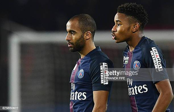 Paris SaintGermain's French midfielder Christopher Nkunku speaks with Paris SaintGermain's Brazilian midfielder Lucas Moura during the French League...