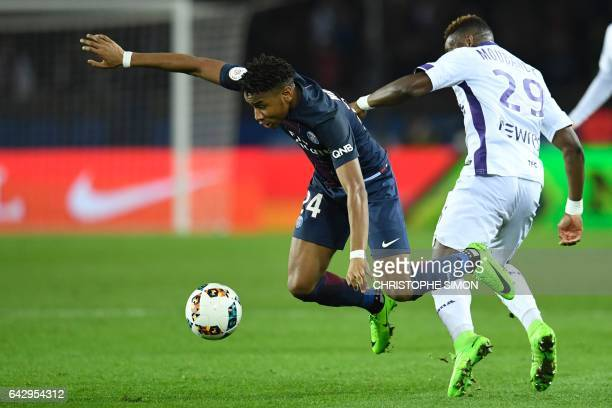 Paris SaintGermain's French midfielder Christopher Nkunku vies with Toulouse's Swiss defender Jacques Francois Moubandje during the French L1...