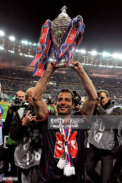 Paris SaintGermain's French Striker Ludovic Giuly holds the trophy to celebrate the winning of the French Cup final between Paris Saint Germain...