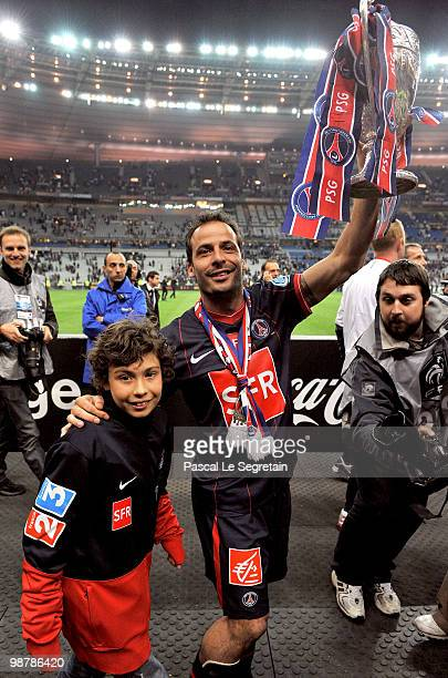 Paris SaintGermain's French Striker Ludovic Giuly with his son holds the trophy to celebrate the winning of the French Cup final between Paris Saint...