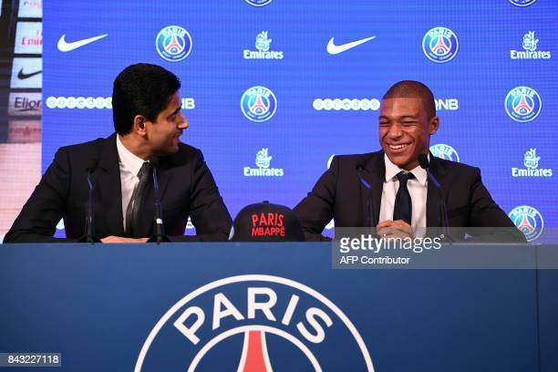 TOPSHOT Paris SaintGermain's new forward Kylian Mbappe is presented by Paris Saint Germain's Qatari president Nasser AlKhelaifi during a press...