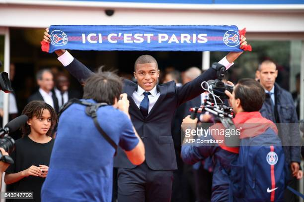 Paris SaintGermain's new forward Kylian Mbappe stands next to his brother Ethan as he holds a PSG fan scarf during his presentation at the Parc des...