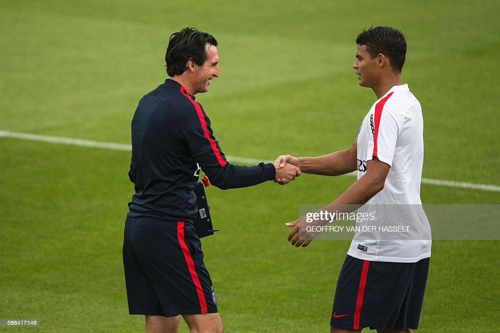 Paris SaintGermain's new Spanish coach Unai Emery shakes hands with Paris SaintGermain's Brazilian defender Thiago Silva during a training session at...