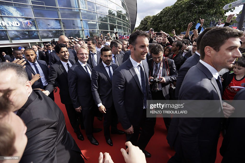 Paris Saint-Germain's owner and president Nasser Al-Khelaifi (3rdL) shakes hands with supporters as he arrives with the squad to parade in a double decker, on May 13, 2013 in Paris, one day after Paris secured French L1 football championship title. AFP PHOTO / KENZO TRIBOUILLARD