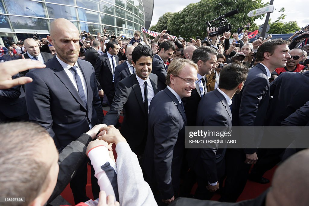 Paris Saint-Germain's owner and president Nasser Al-Khelaifi (2ndL) shakes hands with supporters as he arrives with the squad to parade in a double decker, on May 13, 2013 in Paris, one day after Paris secured French L1 football championship title.