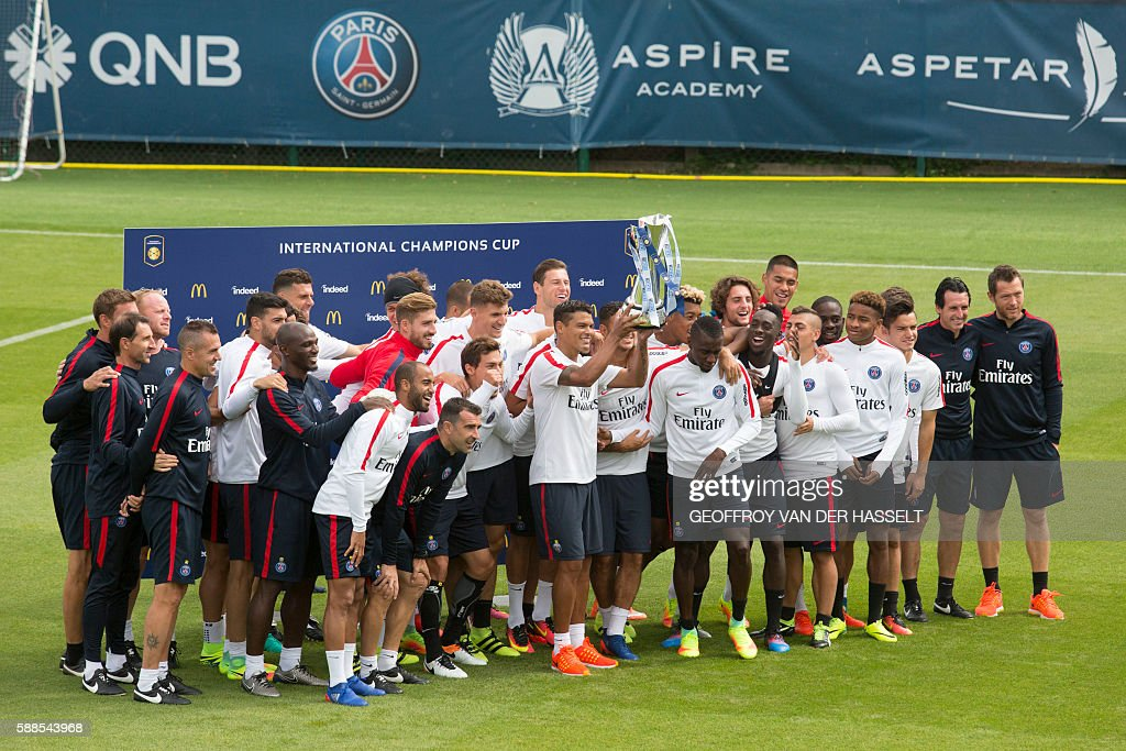Paris SaintGermain's players pose with the 2015 International Champions Cup trophy prior to a training session at the CampdesLoges in...