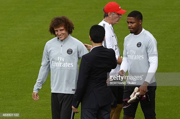 Paris SaintGermains Qatari president Nasser AlKhelaifi is seen from the back as he congradulates PSG's newly recruited Brazilian defender David Luiz...