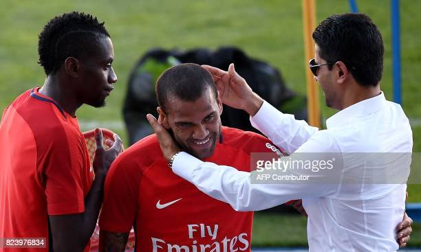 Paris SaintGermain's Qatari president Nasser AlKhelaifi speaks with Paris SaintGermain's Brazilian defender Dani Alves at the end of a training...