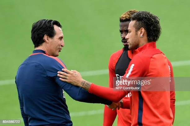 Paris SaintGermain's Spanish coach Unai Emery shakes hands with PSG's Brazilian forward Neymar during a training session at the Camp des Loges in...