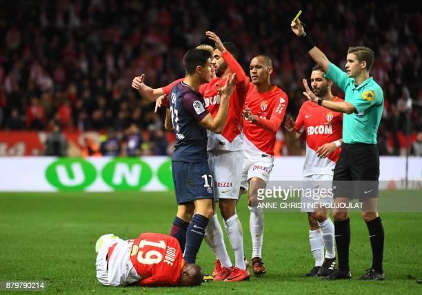 Paris SaintGermain's Spanish defender Yuri Berchiche receives a yellow card from referee Francois Letexier as Monaco's French defender Djibril Sidibe...