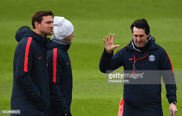 Paris SaintGermain's Spanish head coach Unai Emery speaks with staff members during a training session on January 28 2017 in SaintGermainenLaye west...