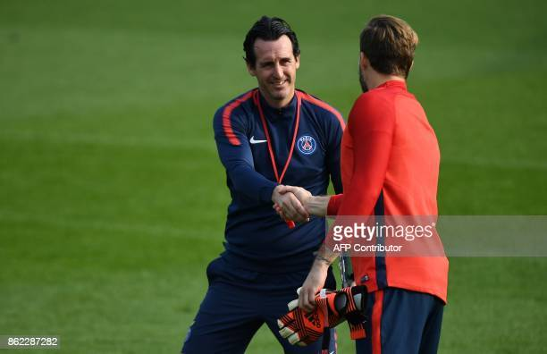 Paris SaintGermain's Spanish headcoach Unai Emery shakes hands with Paris SaintGermain's German goalkeeper Kevin Trapp as they take part in a...