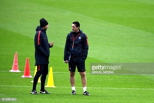 Paris SaintGermain's spanish headcoach Unai Emery talks with a member of the staff during a training session at the Ooredoo PSG training center on...