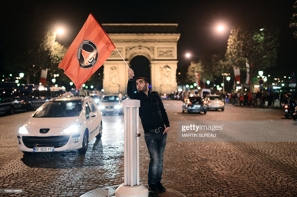 A Paris Saint-Germain's supporter waves a flag as he celebrates the club's championship title on May 13, 2013 on the Champs-Elysees avenue in Paris, one day after Paris secured French L1 football championship title. AFP PHOTO MARTIN BUREAU