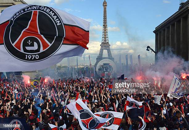 Paris SaintGermain's supporters cheer as their team parades on a bus on May 13 2013 in Paris one day after Paris secured French L1 football...