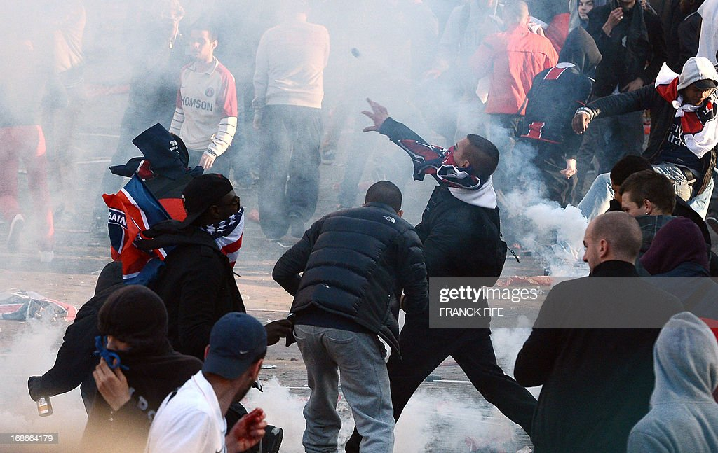 Paris SaintGermain's supporters throw projectiles during clashes with the police on May 13 2013 in Paris one day after Paris secured French L1...