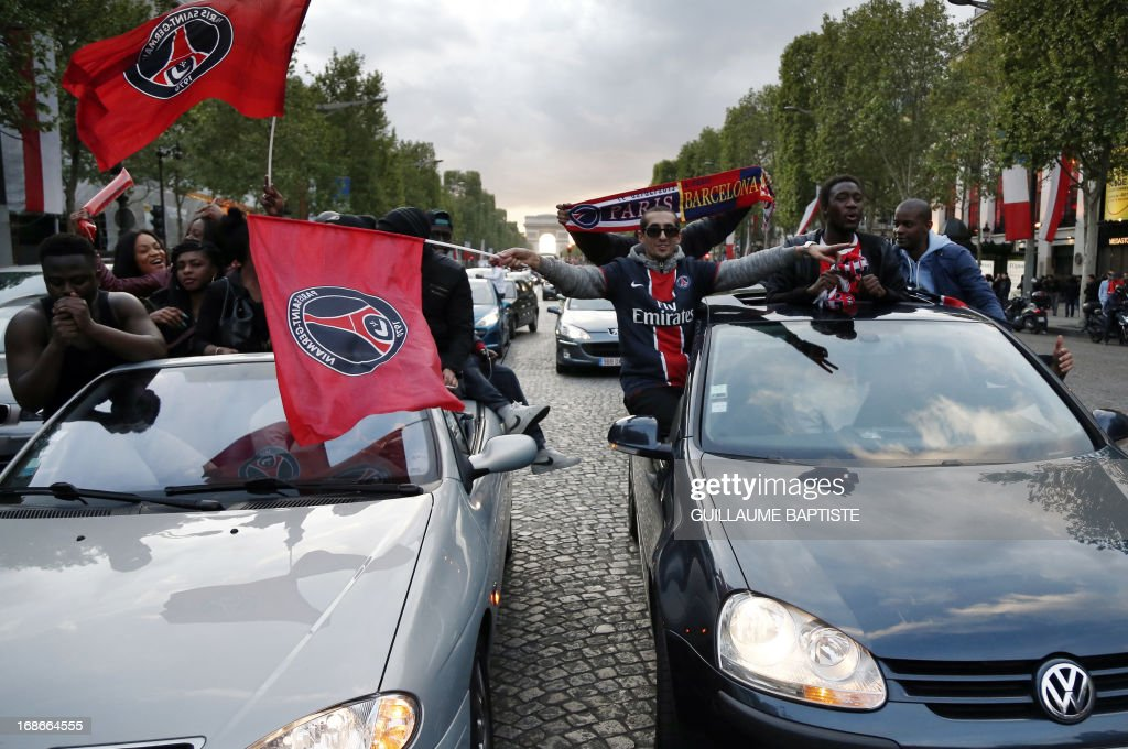 Paris Saint-Germain's supporters wave flags as they celebrate the club's championship title on May 13, 2013 on the Champs-Elysees avenue in Paris, one day after Paris secured French L1 football championship title. AFP PHOTO / GUILLAUME BAPTISTE