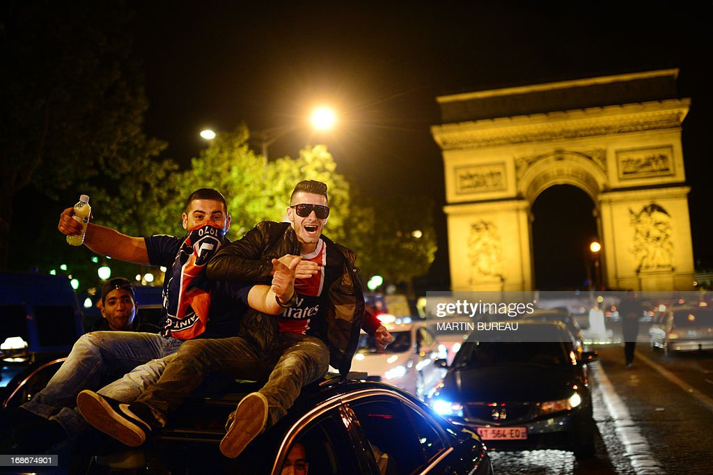 Paris Saint-Germain's supporters wave flags as they celebrate the club's championship title on May 13, 2013 on the Champs-Elysees avenue in Paris, one day after Paris secured French L1 football championship title. AFP PHOTO MARTIN BUREAU