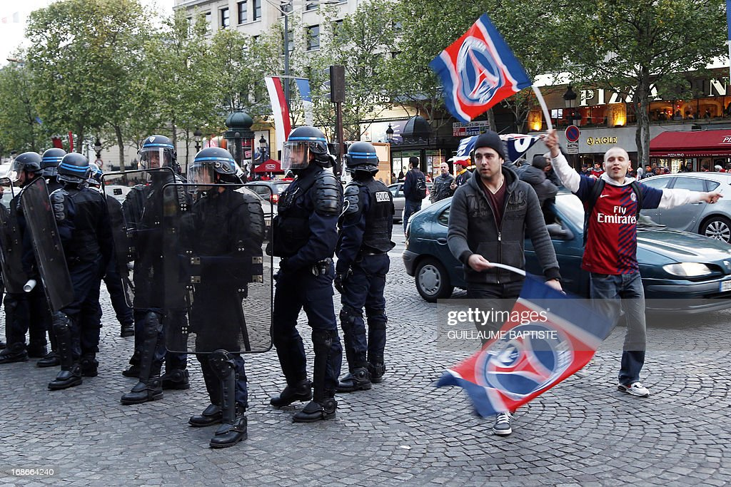 Paris Saint-Germain's supporters wave flags past riot policemen as they celebrate the club's championship title on May 13, 2013 in Paris, one day after Paris secured French L1 football championship title.
