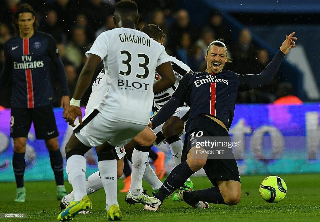 Paris Saint-Germain's Swedish forward Zlatan Ibrahimovic (R) falls during the French L1 football match between Paris Saint-Germain and Rennes at the Parc des Princes stadium in Paris on April 30, 2016. / AFP / FRANCK