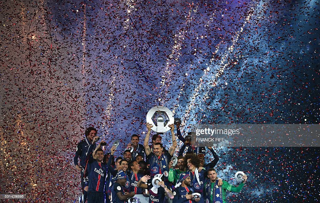 TOPSHOT Paris SaintGermain's Swedish forward Zlatan Ibrahimovic holds the trophy on the podium after winning the French L1 title at the end of the...