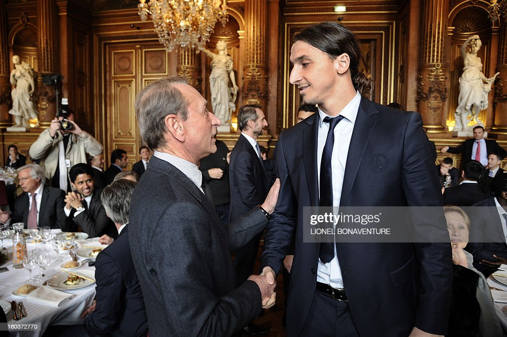 Paris Saint-Germain's Swedish forward Zlatan Ibrahimovic (R) speaks with Paris' mayor Bertrand Delanoe during the annual lunch of the Paris-Saint-Germain's French L1 football club (PSG) team at the Paris city hall, on January 30, 2013.