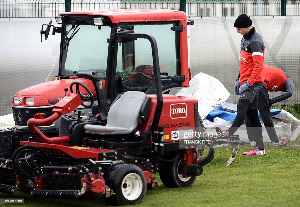 Paris Saint-Germain's Swedish forward Zlatan Ibrahimovic (R) stretches against a small tractor during a training session on January 30, 2013 at the Camp des Loges in Saint-Germain-en-Laye, west of Paris.