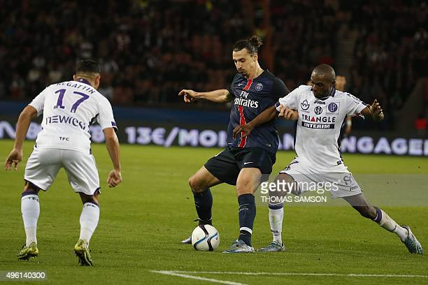 Paris SaintGermain's Swedish forward Zlatan Ibrahimovic vies with Toulouse's French Ivorian defender Jean AkpaAkpro and Toulouse's French Moroccan...