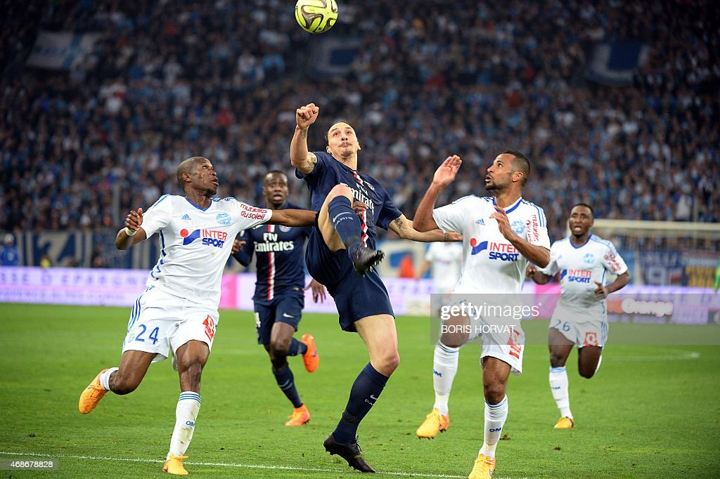 Paris SaintGermain's Swedish midfielder Zlatan Ibrahimovic vies for the ball with Marseille's French defender Rod Fanni and Marseille's Togolese...