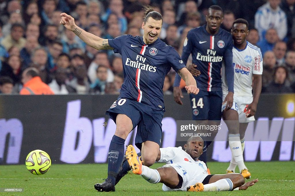 Paris SaintGermain's Swedish midfielder Zlatan Ibrahimovic vies for the ball with Marseille's French defender Rod Fanni during the French L1 football...