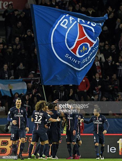 Paris SaintGermain's teammates congratulate after Argentinian midfielder Ezequiel Lavezzi opened the scoring as supporters wave a giant PSG flag...