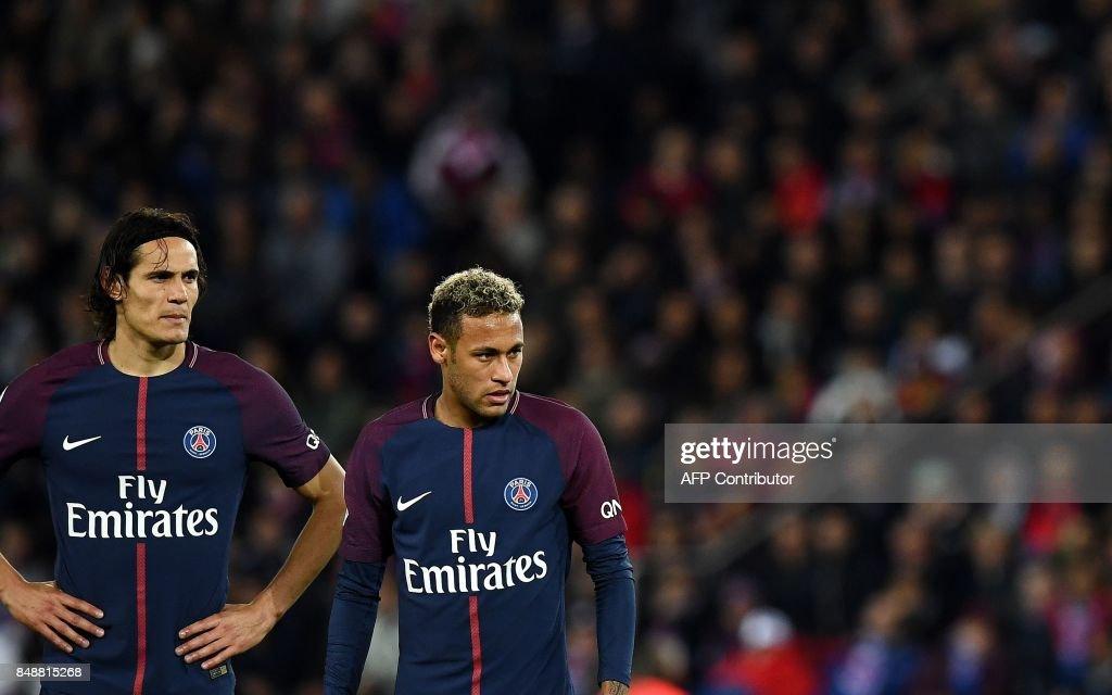 Paris Saint-Germain's Uruguayan forward Edinson Cavani (L) and Paris Saint-Germain's Brazilian forward Neymar react during the French Ligue 1 football match between Paris Saint-Germain (PSG) and Lyon (OL) on September 17, 2017 at the Parc des Princes stadium in Paris. /