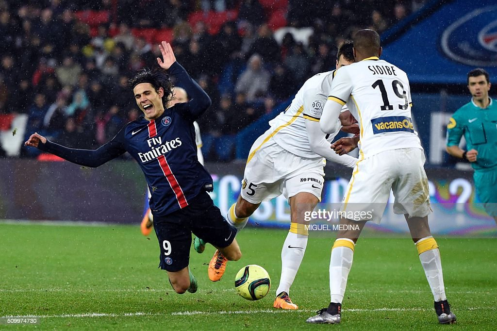 Paris SaintGermain's Uruguayan forward Edinson Cavani falls after being tackled by is tackled by Lille's Argentinian defender Renato Civelli during...