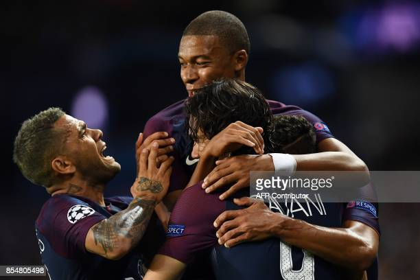 TOPSHOT Paris SaintGermain's Uruguayan forward Edinson Cavani is congratulated by tem mates Paris SaintGermain's French forward Kylian Mbappe and...