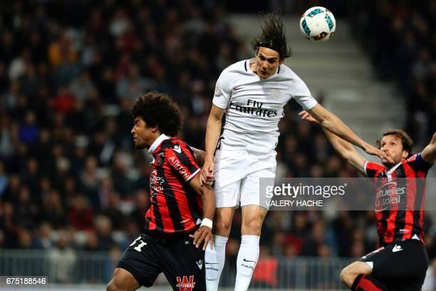 Paris SaintGermain's Uruguayan forward Edinson Cavani vies for the ball with Nice's Brazilian defender Dante and Nice's French defender Paul Baysse...