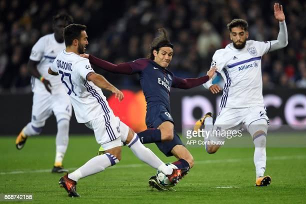 TOPSHOT Paris SaintGermain's Uruguayan forward Edinson Cavani vies for the ball with Anderlecht's Serbian defender Ivan Obradovic and Anderlecht's...