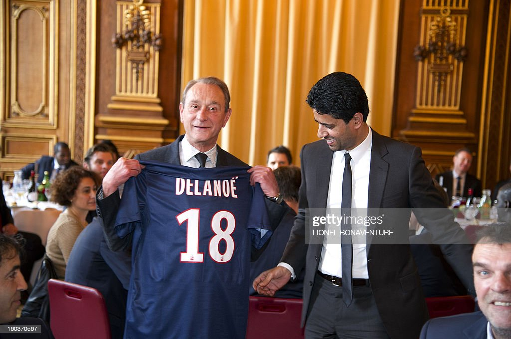 Paris' Socialist mayor Bertrand Delanoe (L) poses with a Paris-Saint-Germain's French L1 football club (PSG) jersey received from chairman of the PSG, Nasser Al-Khelaifi (R) of Qatar, during the annual lunch of the PSG team at the Paris city hall, on January 30, 2013.