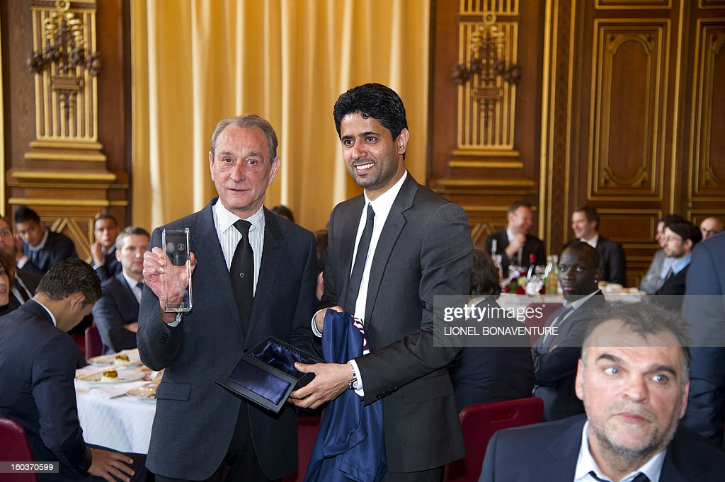 Paris' Socialist mayor Bertrand Delanoe (L) poses with a trophy received from Paris-Saint-Germain's French L1 football club (PSG) chairman, Nasser Al-Khelaifi (R) of Qatar, during the annual lunch of the PSG team at the Paris city hall, on January 30, 2013. AFP PHOTO / LIONEL BONAVENTURE