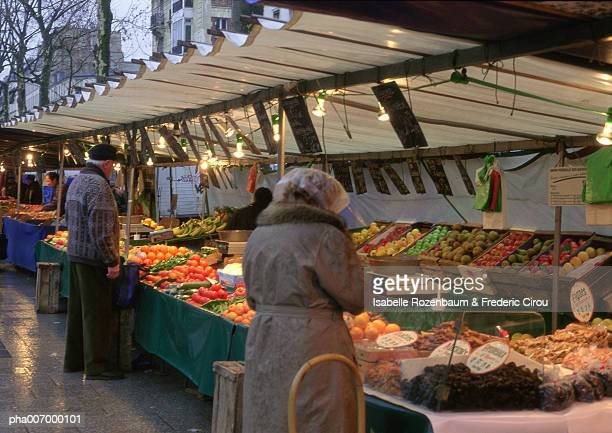 Paris, street produce market, two elderly people, rear view, facing stalls