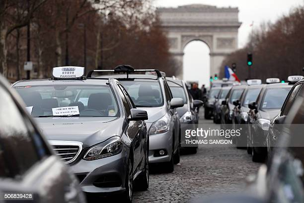 Paris taxi drivers demonstrate on January 26 2016 in Paris to protest against competition from taxi app company Uber and other nonlicensed private...