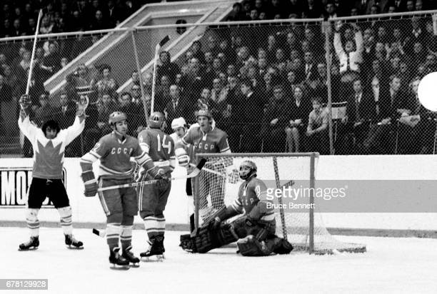 P Parise and Red Berenson of Canada celebrate as Yevgeny Mishakov Yuri Shatalov and goalie Vladislav Tretiak of the Soviet Union look dejected during...