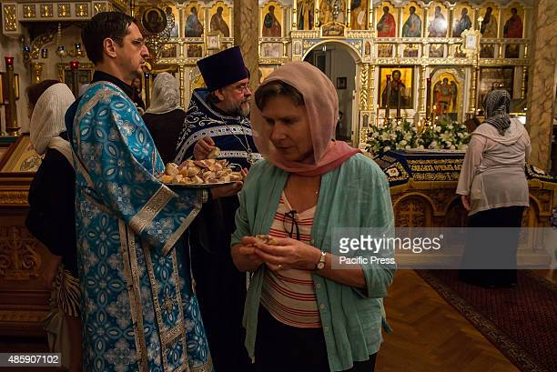 A parishioner receives a morsel of sacramental bread after being anointed with oil On the eve of the Feast of the Dormition of the Virgin the twelfth...