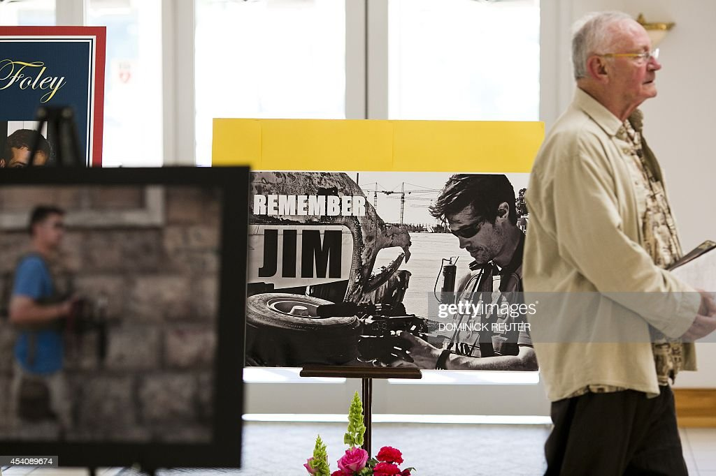A parishioner walks past a display of photos of James Foley before a Catholic mass at Our Lady of the Holy Rosary Parish August 24, 2014 in Rochester, New Hampshire. The family and friends of murdered US journalist James Foley are attending the memorial mass and offering prayers for the safety of his fellow hostages in Syria.