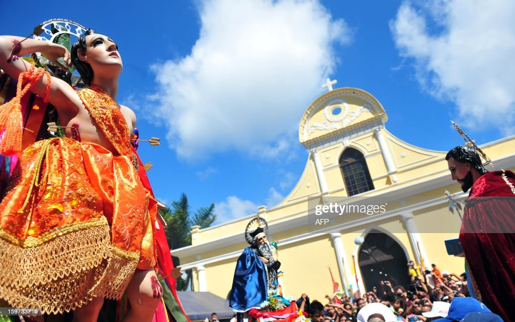 Parishioners carry the image of Saint Sebastian (L) during festivities in his honor, in Diriamba, about 42 km south of Managua, on January 19, 2013. Diriamba's patron saint's image is carried in pilgrimage from Diriamba to Dolores during festivities. AFP PHOTO/Hector RETAMAL