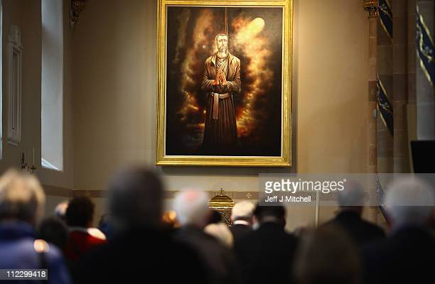 Parishioners pray beneath a painting of St John Ogilvie by artist Peter Howson during mass at the newly refurbished Saint Andrew's Metropolitan...