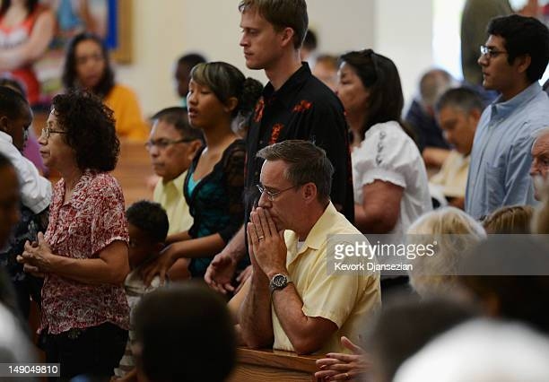 Parishioners pray during morning mass remembering victims of the theater shooting at the Queen of Peace Catholic Church on July 22 2012 in Aurora...