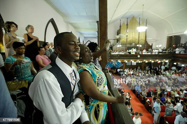 Parishioners Shakur Francis left and Karen WatsonFleming sing as they attend the first church service four days after a mass shooting that claimed...
