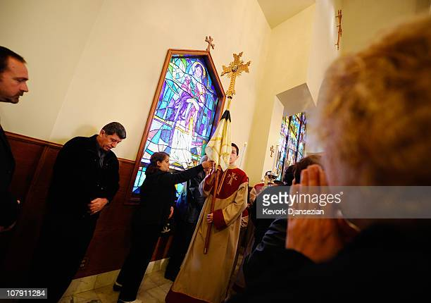 Parishioners touch and kiss the veil of the cross during a Christmas mass procession at St Garabed Armenian Apostolic Church on January 6 2011 in Los...